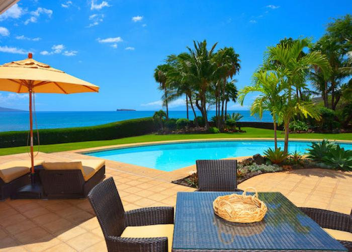 Outdoor dining next to pool with ocean views