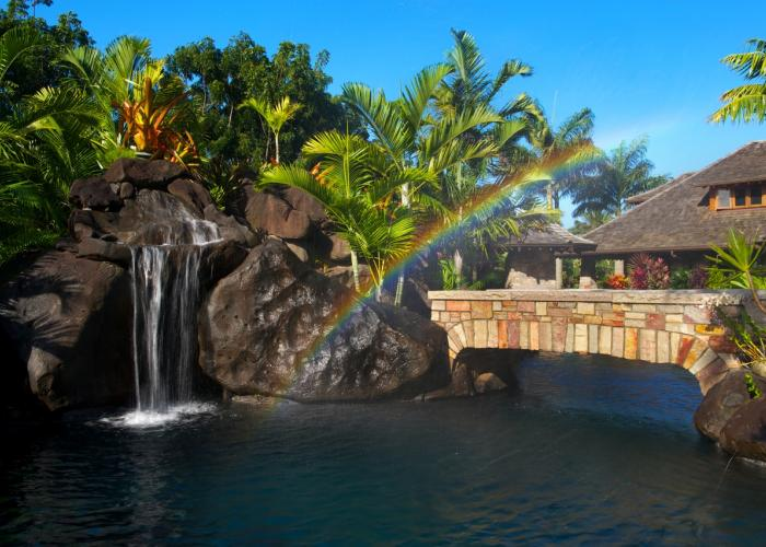 Waterfall and pool with rainbow over bridge